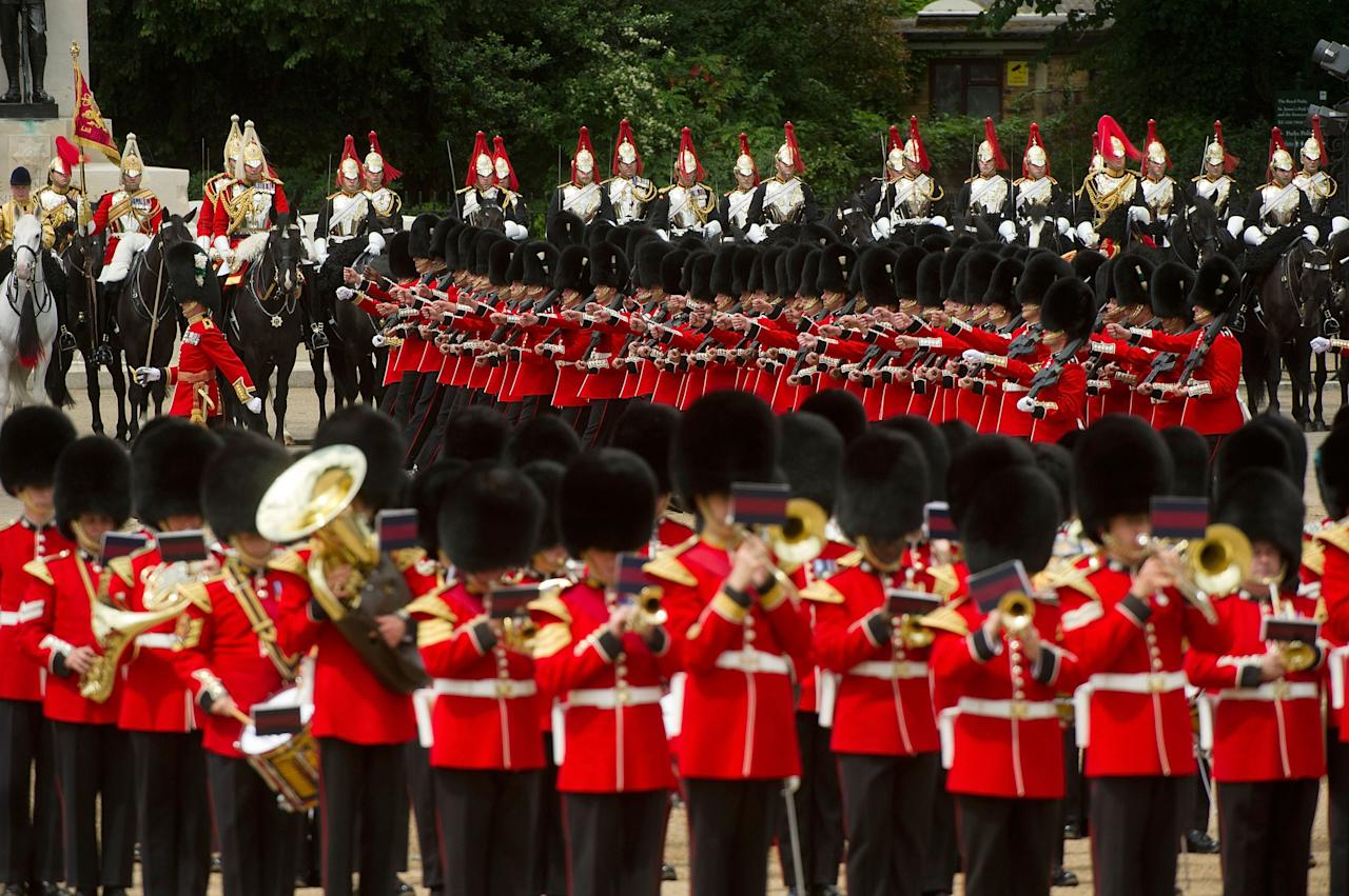 LONDON, ENGLAND - JUNE 15: Members of the Queen's Guard marching during the Trooping Of The Colour at Horse Guards Parade on June 15, 2013 in London, England. Today's ceremony which marks the Queens official birthday will not be attended by Prince Philip the Duke of Edinburgh as he recuperates from abdominal surgery and will also be The Duchess of Cambridge's last public engagement before her baby is due to be born next month. (Photo by Bethany Clarke/Getty Images)