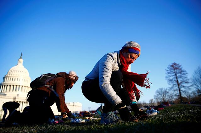 <p>Activists install 7000 shoes on the lawn in front of the U.S. Capitol on Capitol Hill in Washington, U.S. March 13, 2018. Organizers said the installation represents the number of lives lost since the shooting at Sandy Hook elementary in Newtown, Connecticut. (Photo: Eric Thayer/Reuters) </p>