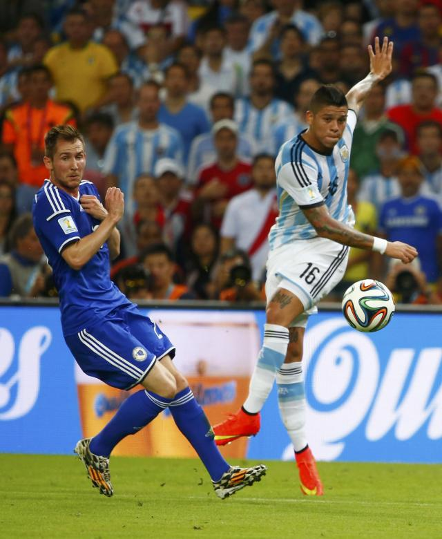 Argentina's Marcos Rojo (R) takes a shot next to Bosnia's Izet Hajrovic during their 2014 World Cup Group F soccer match at the Maracana stadium in Rio de Janeiro June 15, 2014. REUTERS/Tony Gentile (BRAZIL - Tags: SOCCER SPORT WORLD CUP)