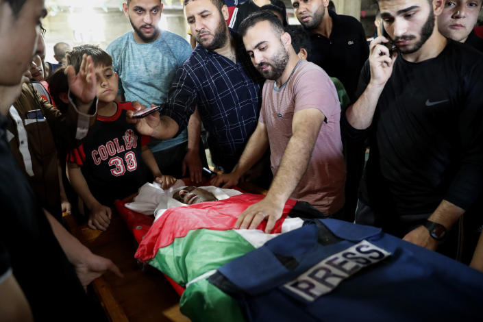 Mourners gather over the body of Yousef Abu Hussein, an al-Aqsa radio reporter, during his funeral at the main mosque in Gaza, Wednesday, May 19, 2021. Abu Hussein was killed during an Israeli airstrike on his house early morning. (AP Photo/Adel Hana)