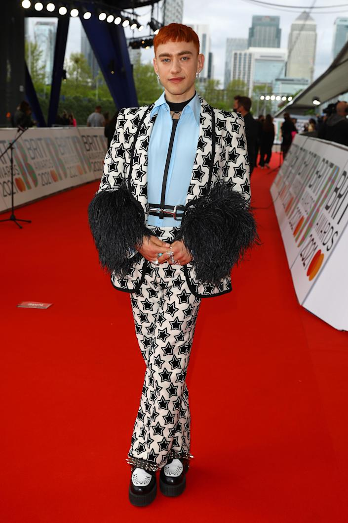 Olly Alexander's red carpet look was quite literally a star-studded black and white Gucci suit with fur-trimmed sleeves. The star was also one of the double fashion servers of the night.