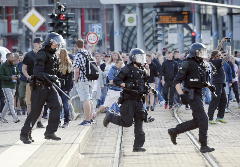 "In this Aug. 27, 2018 photo police officers run during protests in Chemnitz, Germany. Authorities in the eastern German city of Chemnitz were braced for rival protests Monday amid tensions over the killing of a man in what police described as a dispute between ""several people of various nationalities."" The killing sparked spontaneous protests by hundreds of people late Sunday in Chemnitz, a city where almost a quarter voted for the far-right Alternative for Germany party last year. (Andreas Seidel/dpa via AP)"