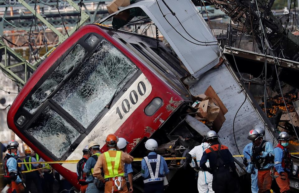 Rescue officers, police and railway company employees work at the scene where a train derailed during a collision with a truck in Yokohama, near Tokyo, Japan September 5, 2019. REUTERS/Issei Kato