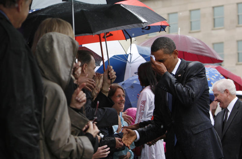 Barack Obama wipes the rain off his face as he meets Pentagon staff and family members of the victims of the September 11 attacks in a ceremony marking the eighth anniversary of the tragedy at the Pentagon in 2009. (Jim Young / Reuters)