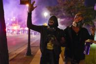 A protesters screams after police use tear gas Friday, Oct. 9, 2020, in Wauwatosa, Wis. On Wednesday, District Attorney John Chisholm refused to issue charges against Wauwatosa Police Officer Joseph Mensah for the Feb. 2 fatal shooting of 17-year-old Alvin Cole at Mayfair Mall. (AP Photo/Morry Gash)