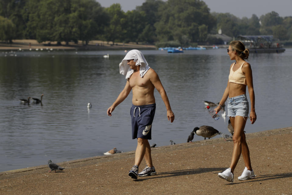 A man keeps cool with a shirt over his head as he walks alongside The Serpentine in Hyde Park in London, Wednesday, Aug. 12, 2020. Thunderstorm warnings are still current for most of the UK on Wednesday, while high temperatures are forecast again for many parts of England. (AP Photo/Kirsty Wigglesworth)