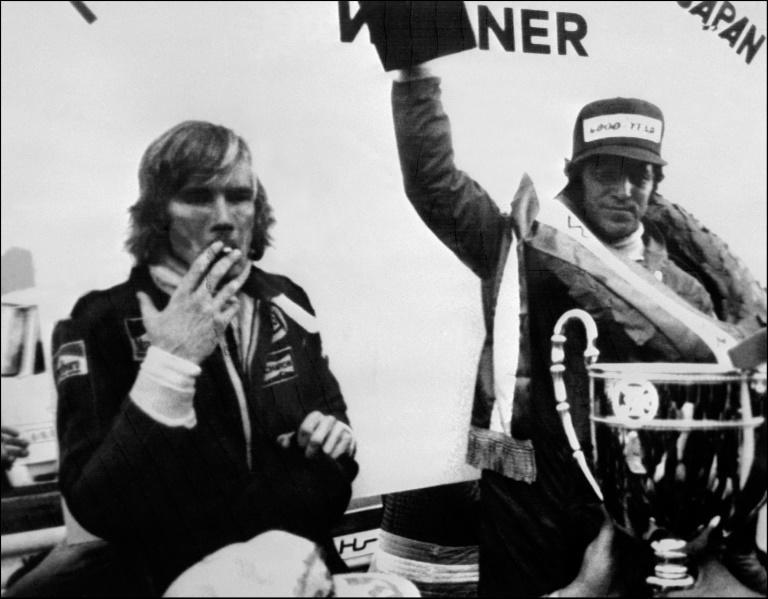 Playing it cool: James Hunt celebrates his world title with a cigarette as Mario Andretti lofts the race winner's trophy at the 1976 Japanese Grand Prix