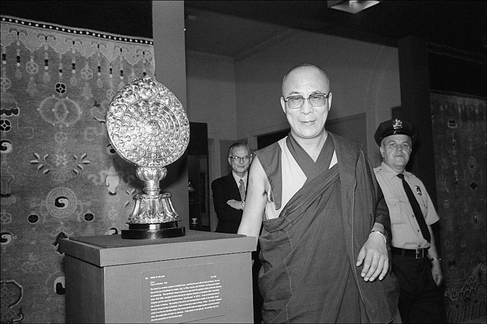 "<p>Dalai Lama as he poses with a silver, 18th Century Tibetan Buddhist Wheel of Law in Newark, New Jersey.<br></p><p>Other celebrity visitors this year: <span class=""redactor-invisible-space"">Joan Jett, Melanie Griffith, Brooke Shields, Steven Bauer and David Niven.<br></span></p>"