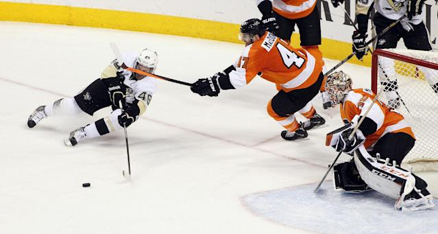 Pittsburgh Penguins' Brian Gibbons, left, loses his edge and the puck trying to shoot as Philadelphia Flyers' Andrew MacDonald, center, and goalie Steve Mason defend during the third period of an NHL hockey game, Saturday, March 15, 2014, in Philadelphia. The Flyers won 4-0. (AP Photo/Tom Mihalek)