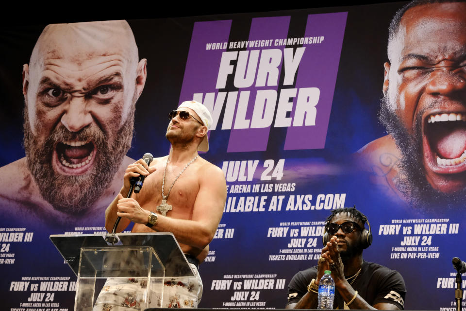 WBC Heavyweight Champion Tyson Fury, left talks during a news conference as Deontay Wilder looks on in Los Angeles on Tuesday, June 15, 2021, in anticipation of their third heavyweight championship showdown scheduled for July 24 in Las Vegas. (AP Photo/Richard Vogel)