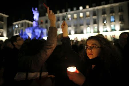 A woman holds a candle to pay tribute during a gathering at the Place Royal in Nantes January 7, 2015, following a shooting by gunmen at the offices of weekly satirical magazine Charlie Hebdo. REUTERS/Stephane Mahe