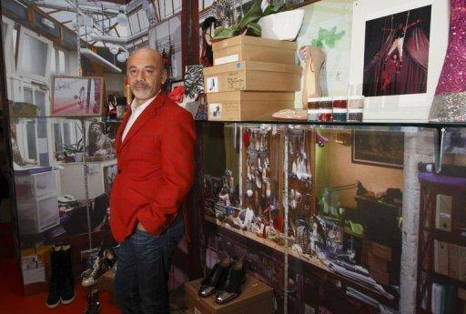 French shoe designer Christian Louboutin poses for a picture at a preview of an exhibition showcasing 20 years of the famous red-soled shoes at the Design Museum in London