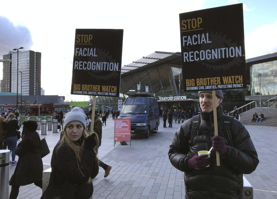 """<span class=""""caption"""">People demonstrate in front of a mobile police facial recognition facility outside a shopping centre in London in February 2020. Dozens of groups and individuals working to protect privacy, human rights and civil liberties want a ban on facial-recognition surveillance by law enforcement and intelligence agencies.</span> <span class=""""attribution""""><span class=""""source"""">AP Photo/Kelvin Chan</span></span>"""