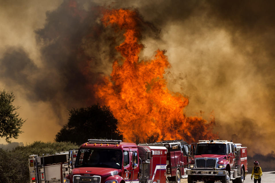 Flames flare behind fire trucks at the Apple Fire in Cherry Valley, Calif., Saturday, Aug. 1, 2020. A wildfire northwest of Palm Springs flared up Saturday afternoon, prompting authorities to issue new evacuation orders as firefighters fought the blaze in triple-degree heat. (AP Photo/Ringo H.W. Chiu)