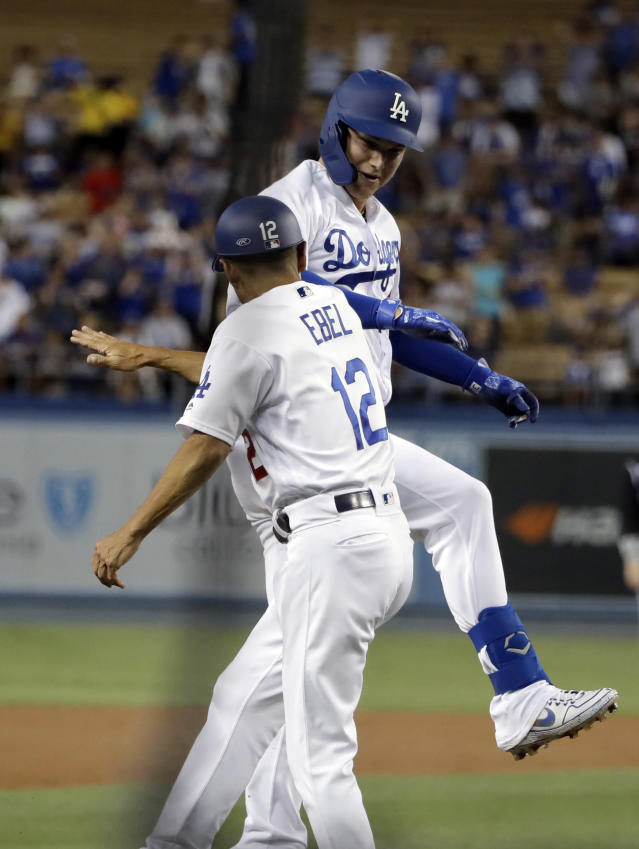 Los Angeles Dodgers' Joc Pederson, top, celebrates his solo home run with third base coach Dino Ebel during the first inning of the team's baseball game against the Colorado Rockies on Wednesday, Sept. 4, 2019, in Los Angeles. (AP Photo/Marcio Jose Sanchez)