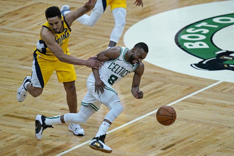 Boston Celtics guard Kemba Walker (8) dribbles the ball upcourt as he is grabbed by Indiana Pacers guard Malcolm Brogdon (7) in the fourth quarter of an NBA basketball game, Friday, Feb. 26, 2021, in Boston. (AP Photo/Elise Amendola)