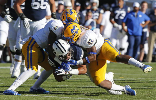 BYU wide receiver Aleva Hifo, center, is tackled by McNeese State's Trent Jackson (9) and Christian Jacobs (42) in the first half during an NCAA college football game Saturday, Sept. 22, 2018, in Provo, Utah. (AP Photo/Rick Bowmer)