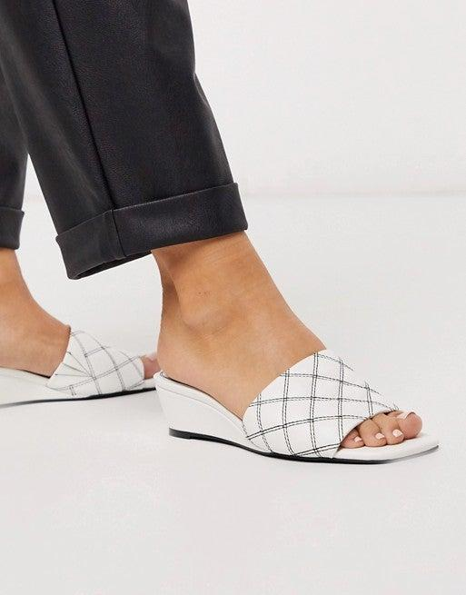 """<h2>ASOS</h2><br><strong>Deal: Extra 20% Off</strong><br>The site's stacked selection of on-sale sandals is already marked down up to 50% off — and now, shoppers can snag an additional 20% off all sale styles with code <strong>""""ASOSSALELOOKS""""</strong>.<br><br><em>Shop <strong><a href=""""https://www.asos.com/us/"""" rel=""""nofollow noopener"""" target=""""_blank"""" data-ylk=""""slk:ASOS"""" class=""""link rapid-noclick-resp"""">ASOS</a></strong></em><br><br><strong>ASOS DESIGN</strong> Thriller quilted demi wedge in white, $, available at <a href=""""https://go.skimresources.com/?id=30283X879131&url=https%3A%2F%2Fwww.asos.com%2Fus%2Fasos-design%2Fasos-design-thriller-quilted-demi-wedge-in-white%2Fprd%2F13922170"""" rel=""""nofollow noopener"""" target=""""_blank"""" data-ylk=""""slk:ASOS"""" class=""""link rapid-noclick-resp"""">ASOS</a>"""