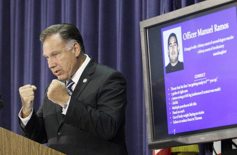 CORRECTS SPELLING OF D.A.'S LAST NAME Orange County, Calif., District Attorney Tony Rackauckas clenches his fists to demonstrate how one officer threatened a homeless man, as he  announces that two police officers will be charged in the death of Kelly Thomas, a mentally ill homeless man, at a news conference in Santa Ana, Calif., Wednesday, Sept. 21, 2011. Fullerton, Calif., police officer Manuel Ramos was charged with one count each of second degree murder and involuntary manslaughter in the death of Thomas after a violent confrontation on July 5 with officers. Police Cpl. Jay Cicinelli was charged with one count each of involuntary manslaughter and excessive force. (AP Photo/Reed Saxon)