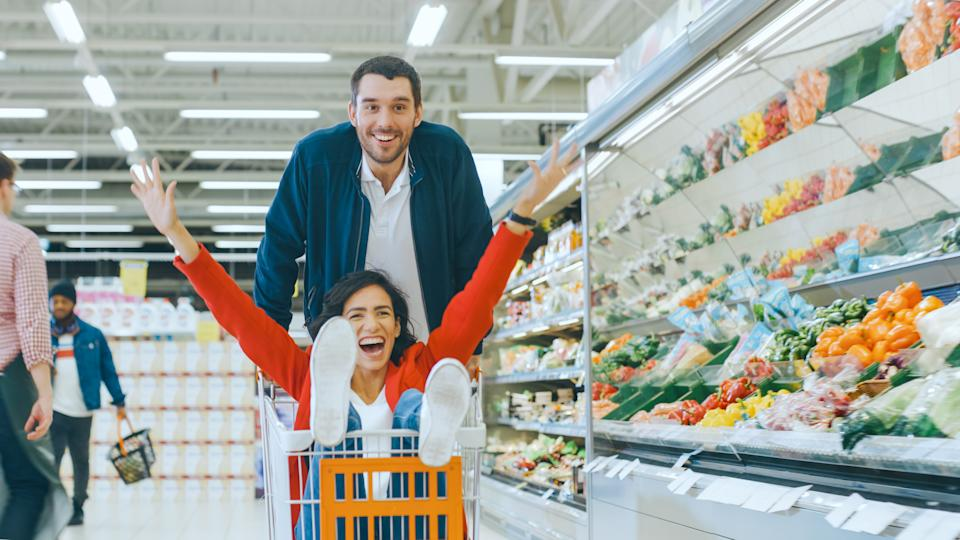 At the Supermarket: Man Pushes Shopping Cart with Woman Sitting in it, Happy Couple Has Fun Racing in a Trolley through the Fresh Produce Section of the Store. People Walking By.