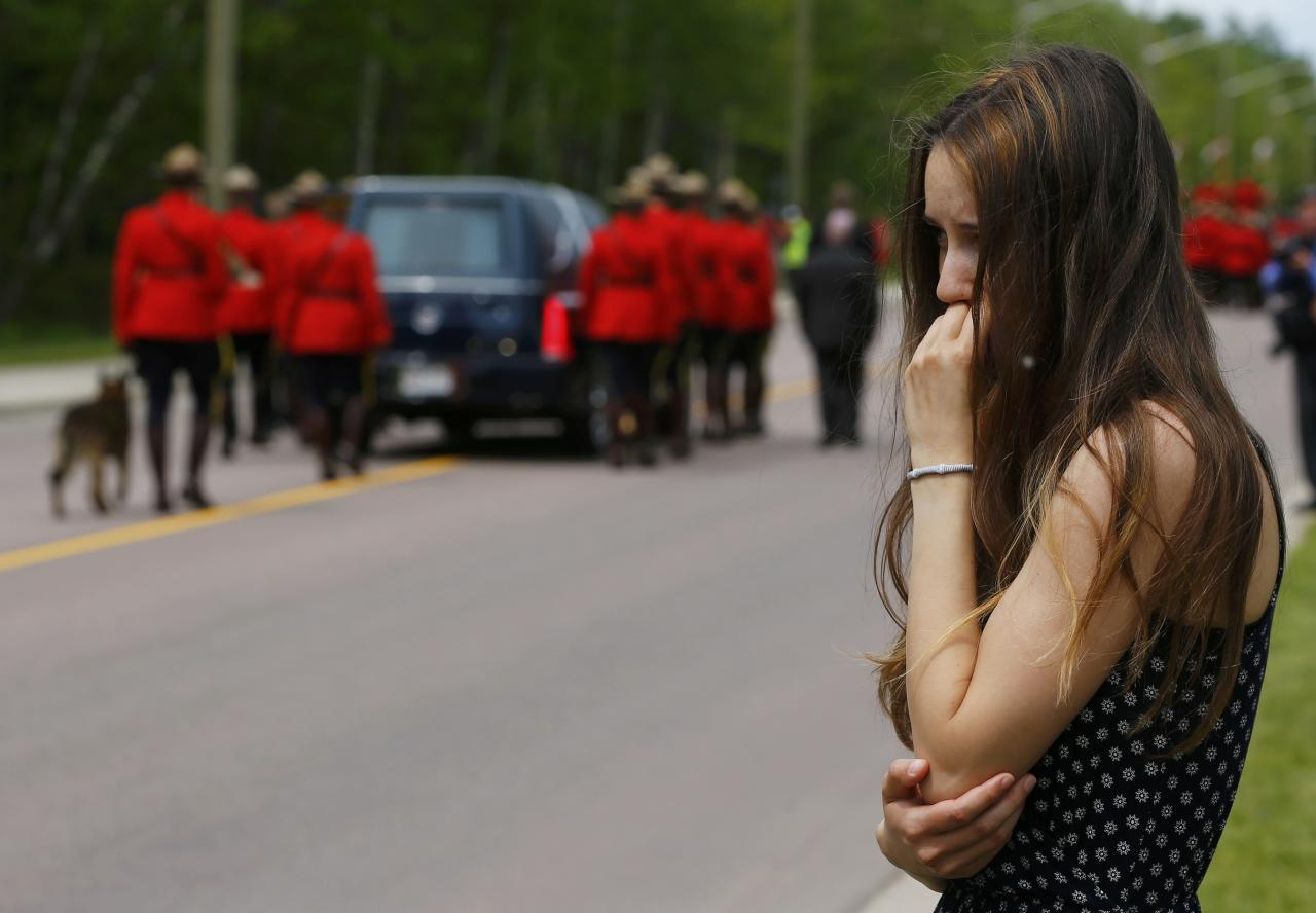 A woman watches the funeral procession for three Royal Canadian Mounted Police officers who were killed last week in Moncton, New Brunswick, June 10, 2014. Justin Bourque, 24, was charged with murder on Friday in the slayings of the three Royal Canadian Mounted Police officers, Constables Fabrice Georges Gevaudan, 45; David Joseph Ross, 32, and Douglas James Larche, 40, during a shooting spree in the eastern Canadian city of Moncton. The shooting spree was one of the worst of its kind in Canada, where gun laws are stricter than in the United States and deadly attacks on police are rare. REUTERS/Mark Blinch (CANADA - Tags: CRIME LAW OBITUARY)