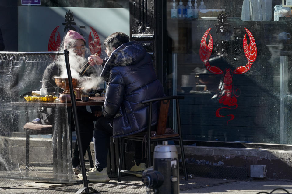 Steam rises from a dish as customers eat a meal on the sidewalk outside a restaurant, Sunday, Jan. 10, 2021, in the Hell's Kitchen neighborhood of New York. The boarded-up windows and For Rent signs are all over the place in Manhattan's Hell's Kitchen neighborhood. Nearby, the Broadway theaters are all dark. But the economic darkness brought on by the coronavirus pandemic has had a few bright spots. A couple of well-loved venues have gotten financial boosts, thanks to online fundraising campaigns and even a telethon. (AP Photo/Mary Altaffer)