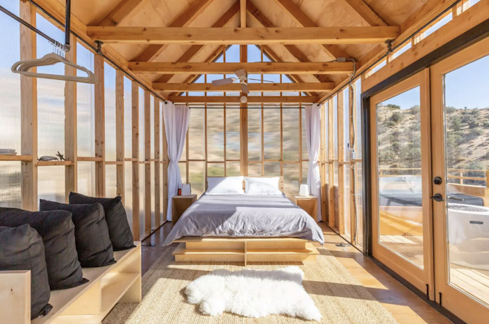 """<h2><a href=""""http://airbnb.pvxt.net/46Oq3"""" rel=""""nofollow noopener"""" target=""""_blank"""" data-ylk=""""slk:Minimalist Modern Cabin"""" class=""""link rapid-noclick-resp"""">Minimalist Modern Cabin</a></h2><br>""""With some of the best views in the high desert, this unique dwelling situated in the hills of yucca valley has everything you could want in a desert getaway. It has its own deck and propane fire pit and is completely off-grid, generating its own power from the sun. The detached kitchen and full bathroom are just yards away. It is one of two other short term rentals on the property."""" <br><br><strong>Location:</strong> Morongo Valley, California<br><strong>Sleeps:</strong> 2<br><strong>Price Per Night:</strong> $226"""