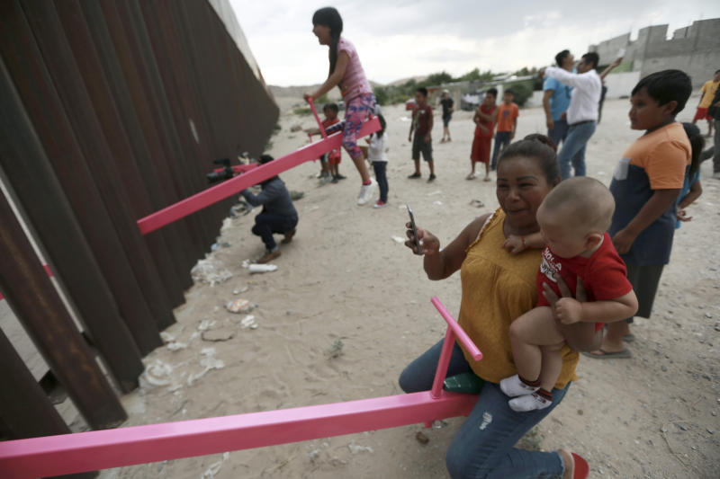 A mother and her baby play on a seesaw installed between the steel fence that divides Mexico from the United States in Ciudad de Juarez, Mexico, Sunday, July 28, 2019. The seesaw was designed by Ronald Rael, a professor of architecture in California. (AP Photo/Christian Chavez)