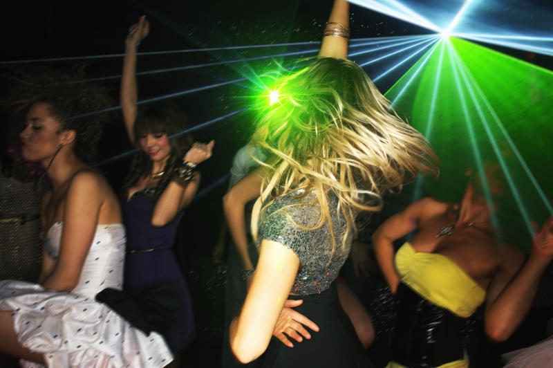 Group of young people dancing in nightclub with laser lighting.