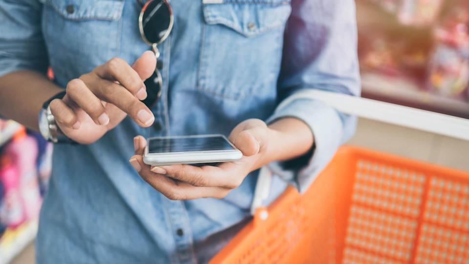 Woman wearing blue jeans shirt and sunglasses using mobile phone to compare price and holding orange shopping basket in mini mart background.