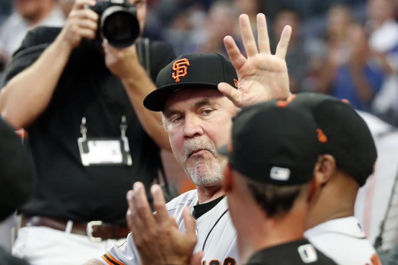 San Francisco Giants manager Bruce Bochy (15) waves to the crowd after a video tribute to him in the first inning of a baseball game against the Atlanta Braves, Friday, Sept. 20, 2019, in Atlanta. Bochy plans to retire at the end of the season. (AP Photo/John Bazemore)