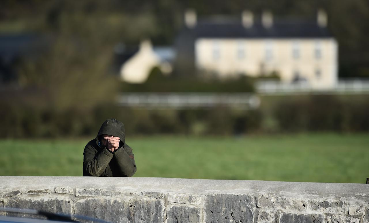 <p>A mourner prays by a wall as family carry the late Dolores O'Riordan from St Ailbe's Church, Ballybricken on Jan. 23, 2018 in Limerick, Ireland. Photo from Charles McQuillan/Getty Images. </p>
