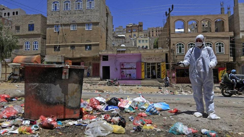 A Yemeni volunteer sprays disinfectant over garbage in the one of Sanaa's impoverished neighbourhoods, on March 30