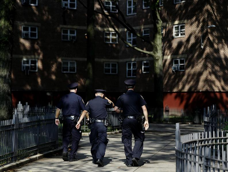 FILE - In this Aug. 13, 2013 file photo, police officers walk through the Brownsville Houses the Brownsville section of Brooklyn, New York. A federal appeals court on Thursday, Oct. 31, 2013, blocked a judge's order requiring changes to the New York Police Department's stop-and-frisk program and removed the judge from the case. (AP Photo/Seth Wenig, File)