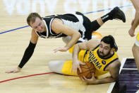 Los Angeles Clippers guard Luke Kennard, left, and Indiana Pacers center Goga Bitadze scramble for a loose ball during the fourth quarter of an NBA basketball game, Sunday, Jan. 17, 2021, in Los Angeles. (AP Photo/Ashley Landis)