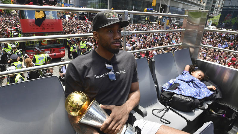 Toronto Raptors forward Kawhi Leonard holds his playoffs MVP trophy as he celebrates while his daughter Kaliyah naps during the 2019 Toronto Raptors Championship parade in Toronto on Monday, June 17, 2019. THE CANADIAN PRESS/Frank Gunn