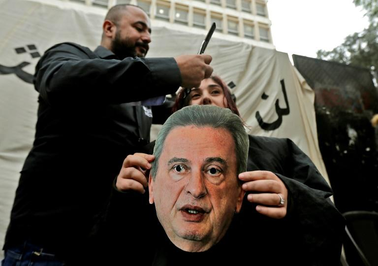A Lebanese anti-government protester holds a mask of Central Bank Governor Riad Salameh as she sits for a haircut in front of the central bank headquarters in Beirut (AFP Photo/JOSEPH EID)