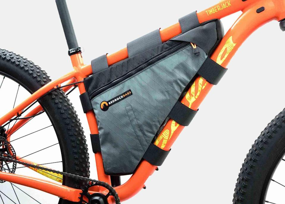 """Bedrock Bags started in 2012 out of co-founder Andrew Wracher's Colorado garage. Some things have changed with the expansion of their business but Bedrock Bags are still made in Durango, Colorado, with USA-made materials, whenever possible. The <a href=""""https://cna.st/affiliate-link/2hc5hQAHwjs1wtyubX1Fg2r23YtFXRA96cPP9KbDCL7UCqgHt6jwdz5ELUpzFaGq6YtnPNCSgFCxUQN1B2aMHV44XQ4rHt6dToUEMr53eoQ?cid=6088358d211142d4f9886bd7"""" rel=""""nofollow noopener"""" target=""""_blank"""" data-ylk=""""slk:custom frame bag"""" class=""""link rapid-noclick-resp"""">custom frame bag</a> is perfect for long trips when you'll need to carry tools, a rain jacket, and even your lunch. To make sure the bag is tailored to your ride, Bedrock uses a modeling system to custom fit your order to your bike. Waterproof zippers, up to 14 liters in space, and 12 colors to choose from—what's not to love? $170, Bedrock Bags. <a href=""""https://www.bedrockbags.com/gear/custom-frame-bag"""" rel=""""nofollow noopener"""" target=""""_blank"""" data-ylk=""""slk:Get it now!"""" class=""""link rapid-noclick-resp"""">Get it now!</a>"""
