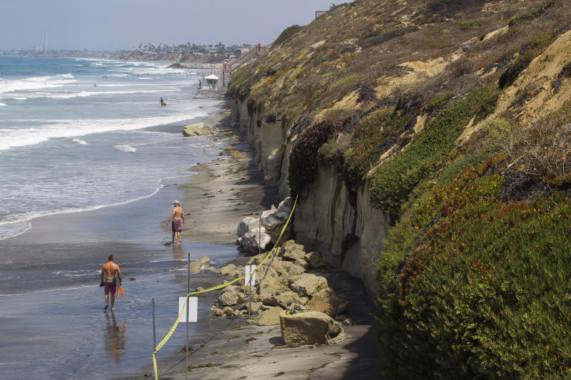 FILE - In this Aug. 3, 2019 file photo the area where a sea cliff collapsed killing three people is taped off near the Grandview Beach access stairway in the beach community of Leucadia, in Encinitas, Calif. Three family members enjoying a day at a San Diego area beach were killed Friday when a huge slab of the cliff above plunged on to the sand. The collapse has raised questions about the stability of bluffs along California's 1,000-mile (1,600-kilometer) coast. (Hayne Palmour IV/The San Diego Union-Tribune via AP,File)