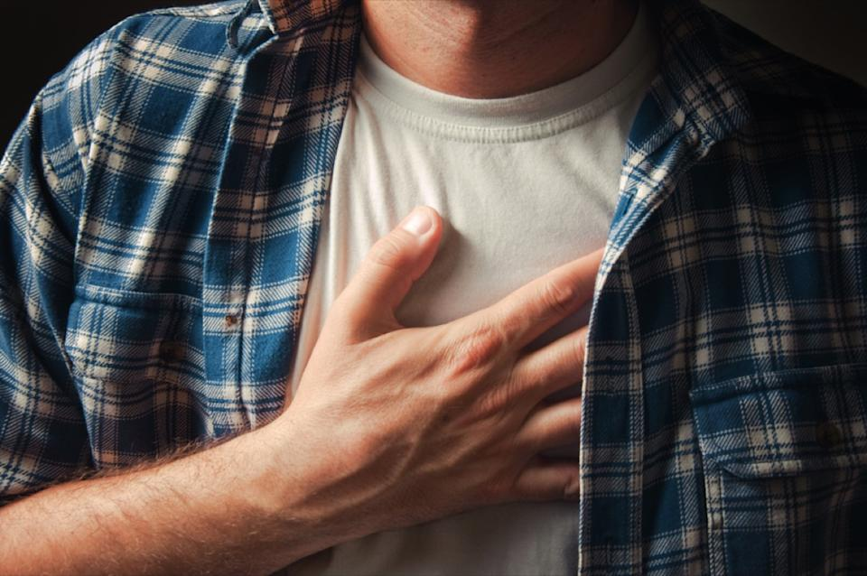Closeup of white man's hand on chest