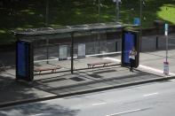 A woman stands alone on a bus stop during a workday following the implementation of stricter social-distancing and self-isolation rules to limit the spread of the coronavirus disease (COVID-19) in Sydney