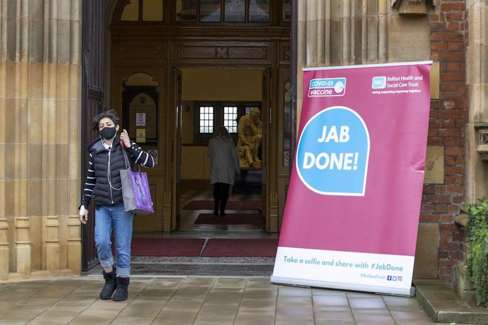 """A woman walks past a Covid-19 """"Jab Done!"""" sign at Queen's University, Belfast (Liam McBurney/PA) (PA Wire)"""