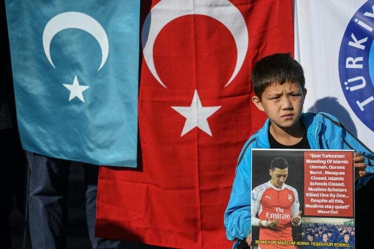 A supporter of China's Muslim Uighur minority holds a placard of Arsenal's Turkish-origin German midfielder Mesut Ozil during a demonstration at Beyazid square in Istanbul