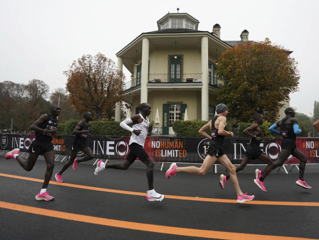 In this photo made available by The INEOS 1:59 Challenge on Saturday, Oct. 12, 2019, Eliud Kipchoge, white vest, runs past the Lusthaus with his pacemaking team in Vienna, Austria. Saturday, Oct. 12, 2019, during his attempt to run a sub two-hour marathon.(Andrew Baker /The INEOS 1:59 Challenge via AP)
