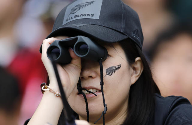 New Zealand All Blacks fan watches her team warm up ahead of the Rugby World Cup Pool B game at Tokyo Stadium between New Zealand and Namibia in Tokyo, Japan, Sunday, Oct. 6, 2019. (AP Photo/Christophe Ena)