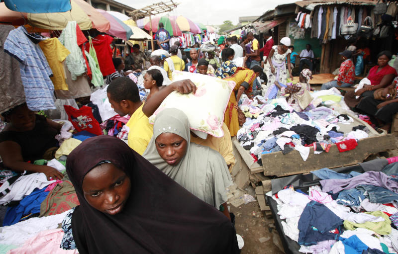 In this photo taken Friday, April. 12, 2013 women walk past people buying second hand clothes at Katangua market in Lagos, Nigeria. The buses crammed full of young men leave each afternoon from this busy market in Nigeria's largest city, some with bruises around their faces and defensive wounds to their arms. The immigrant labor that makes Katangua Market in Lagos thrum along each day between piles of secondhand clothes and down narrow dirt alleyways remains in fear after a series of raids by Nigerian authorities in recent days. Immigrant workers here and elsewhere, those largely from neighboring Niger to the north, find themselves targeted by security agencies anxious about a growing Islamic extremist insurgency in Nigeria that could spread southward. (AP Photo/Sunday Alamba)