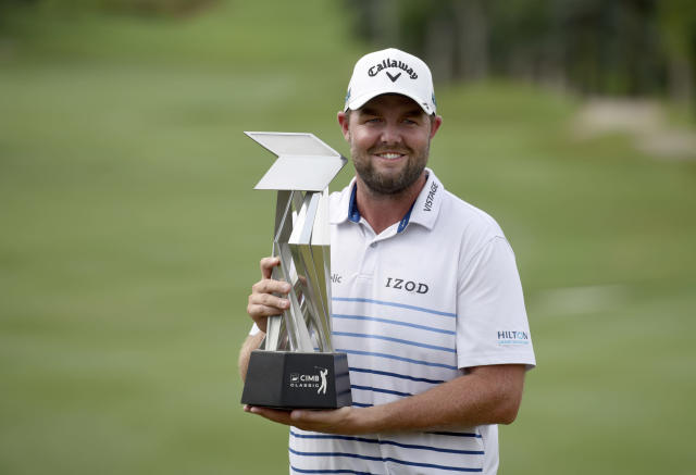 Marc Leishman of Australia poses with his trophy after winning the CIMB Classic golf tournament at Tournament Players Club (TPC) in Kuala Lumpur, Malaysia, Sunday, Oct. 14, 2018. (AP Photo/Yam G-Jun)