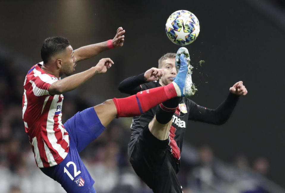 Atletico Madrid's Renan Lodi, left, fights for the ball against Leverkusen's Mitchell Weiser during the Champions League Group D soccer match between Atletico Madrid and Bayer Leverkusen at Wanda Metropolitano stadium in Madrid, Spain, Tuesday, Oct. 22, 2019. (AP Photo/Bernat Armangue)