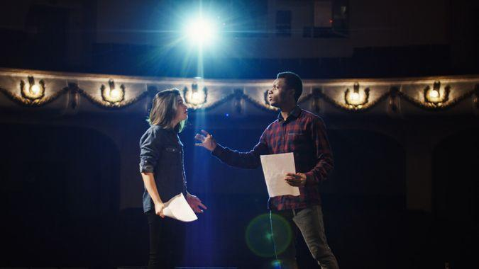Medium shot of an actor and actress rehearsing a scene in the theater while holding their scripts.