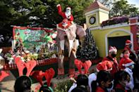 An elephant from the Ayutthaya Elephant Palace, dressed in a Santa Claus costume and wearing a face mask, is greeted by students during an event to hand out masks at a school in Ayutthaya, Thailand